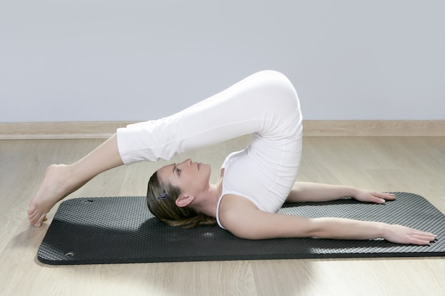 Mooie vrouw in zwarte mat yoga in de sportschool