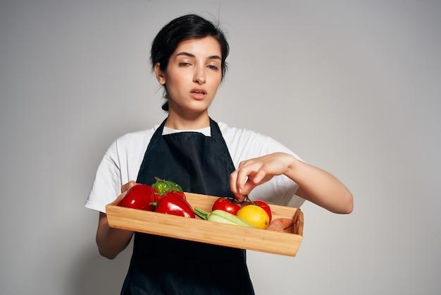 Mooie vrouw in zwarte schorten groenten die thuis koken