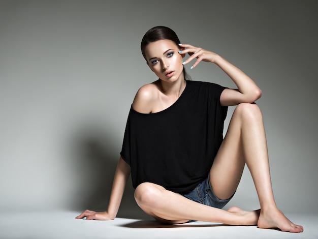 Mooie vrouw in zwarte t-shirt en jeansborrels.
