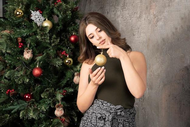 Mooie vrouw in zwarte top poseren met gouden bal in de buurt van kerstboom