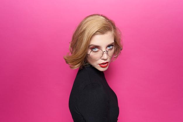 Mooie vrouw in zwarte trui rode lippen in glazen emoties roze achtergrond.
