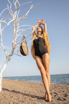 Mooie vrouw in zwarte zwembroek op het strand