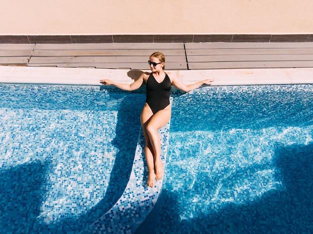 Mooie vrouw in zwembad in hotel