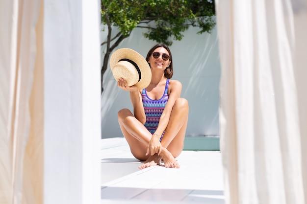 Mooie vrouw in zwembroek bij het zwembad in de achtertuin op een zonnige zomerdag, genietend van geweldig warm weer, het vangen van zonnestralen