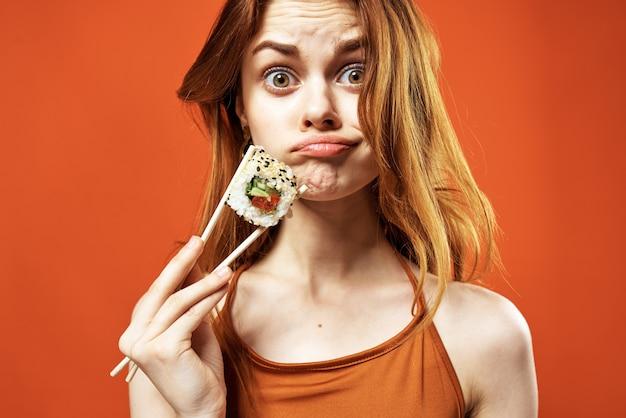 Mooie vrouw japanse eetstokjes sushi rolt dieet emoties