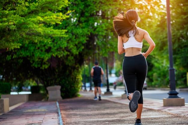 Mooie vrouw jogger buiten leven gezonde levensstijl in stadspark.