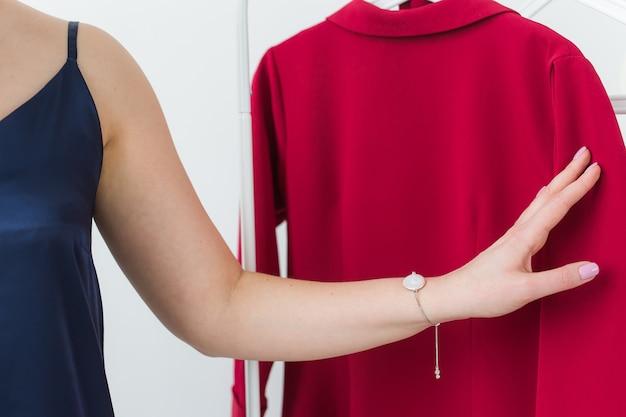 Mooie vrouw jurk kijken tijdens het kiezen van een geschikte