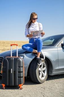 Mooie vrouw kaart voor reizen. mooi meisje dat naast de auto staat. het plezier van reizen