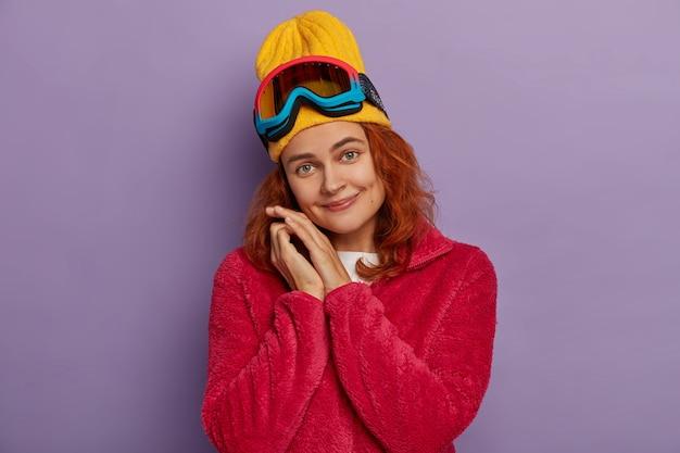 Mooie vrouw kantelt hoofd, draagt gele hoed en rode jas, heeft plezier, gebruikt snowboardbril kijkt graag naar camera geïsoleerd op violette muur