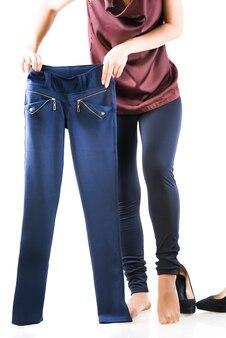 Mooie vrouw kiest de juiste broek. concept van het kiezen van dingen voor het gewenste evenement uit de garderobecollectie