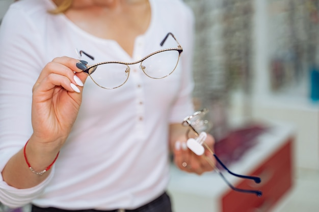 Mooie vrouw kiest nieuwe leesbril in opticien winkel