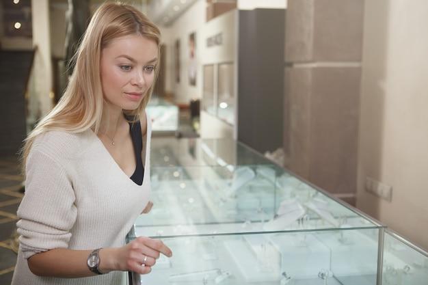 Mooie vrouw kijken naar sieraden te koop tentoongesteld in juwelier, kopie ruimte