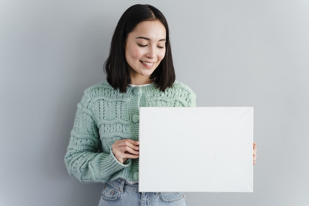 Mooie vrouw kijkt naar een stuk papier in haar hand