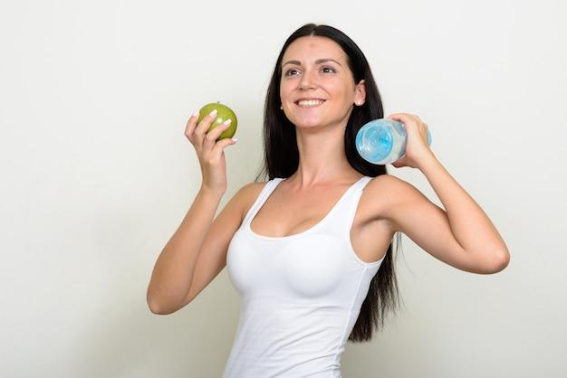 Mooie vrouw klaar voor sportschool tegen witte muur