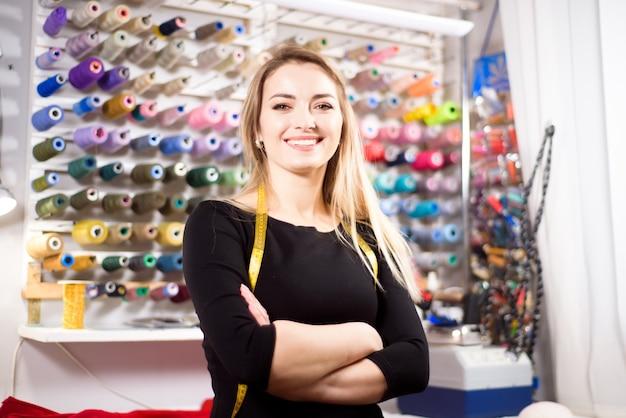 Mooie vrouw kleermaker op achtergrond van gekleurde spoelen van draad voor naaien en borduren.