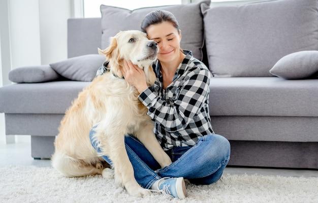 Mooie vrouw knuffelen mooie hond in lichte kamer