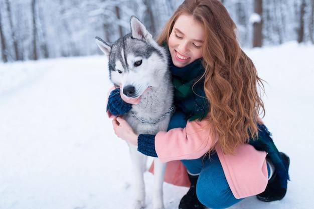 Mooie vrouw knuffels met siberische husky