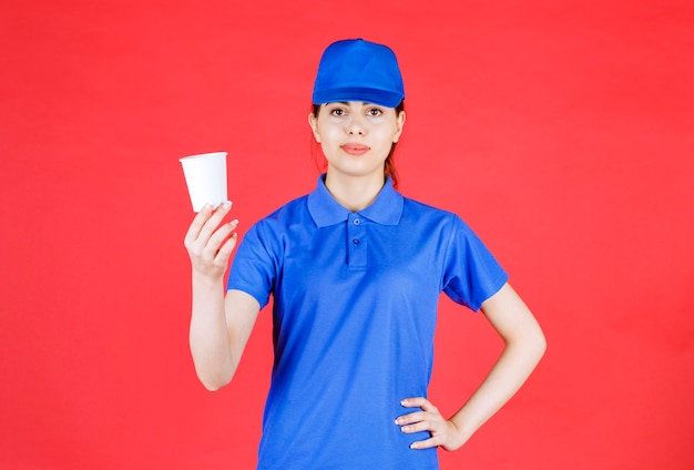 Mooie vrouw koerier in blauwe outfit poseren met kopje thee op rood.