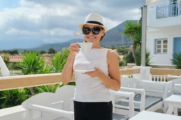 Mooie vrouw koffie drinken buitenshuis