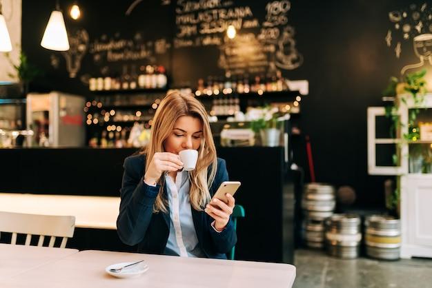Mooie vrouw koffie drinken en het gebruik van de telefoon in het restaurant.