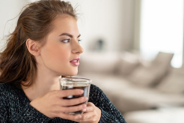 Mooie vrouw koffie drinken in de ochtend thuis