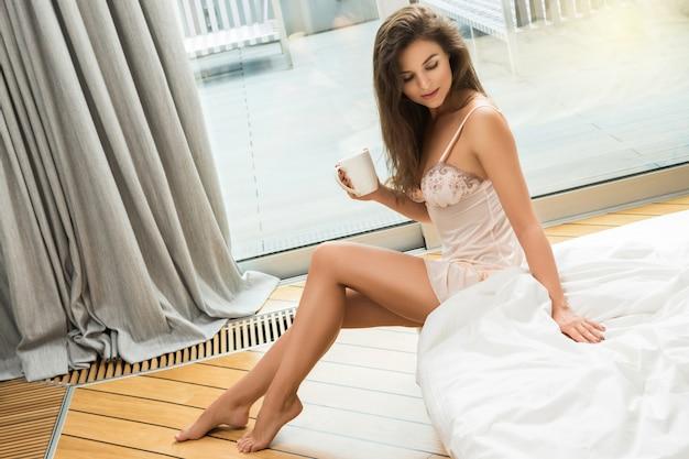 Mooie vrouw koffie of thee drinken in de slaapkamer