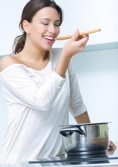 Mooie vrouw koken in de keuken