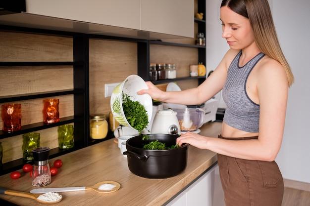 Mooie vrouw koken in moderne keuken