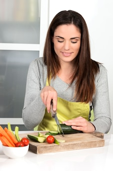 Mooie vrouw komkommer en groenten snijden in de keuken