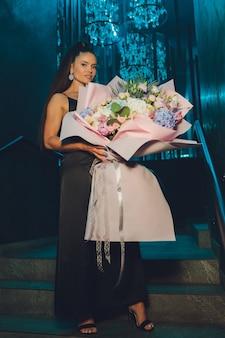 Mooie vrouw kreeg cadeautjes voor haar verjaardagsfeestje en bloemen om een goede foto te maken