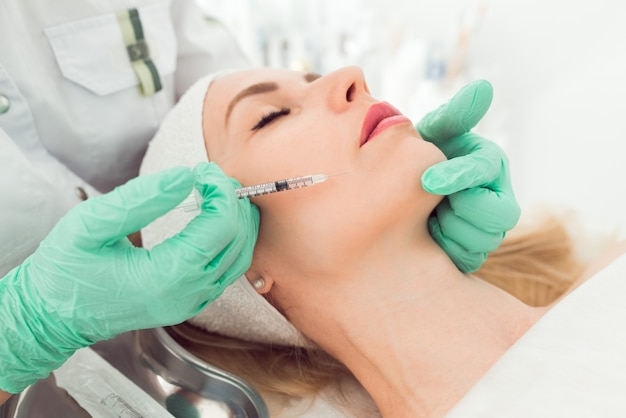Mooie vrouw krijgt botoxinjectie in haar gezicht