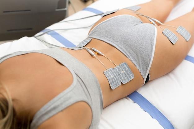 Mooie vrouw krijgt elektrostimulatie therapie, anti-cellulitis en anti-vettherapie op haar strakke billen in de schoonheidssalon