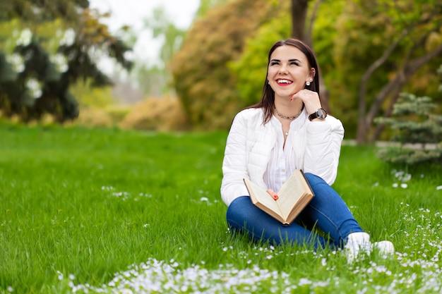 Mooie vrouw lachen, zittend op het gras en het lezen van een boek