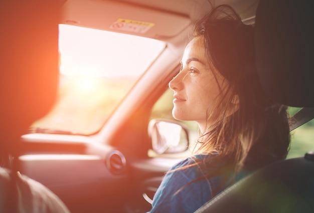 Mooie vrouw lachend zittend op de voorste passagiersstoelen in de auto