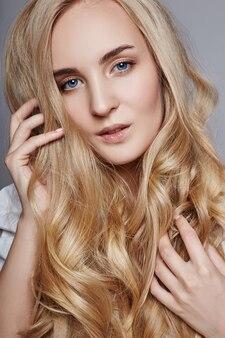 Mooie vrouw lang haar kleuren in ultra blonde, natuurlijke make-up.