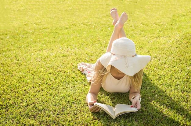 Mooie vrouw leesboek liggend op het gazon, van bovenaf gezien met zomerhoed.