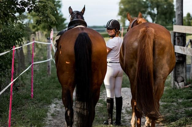 Mooie vrouw leidt paarden van trainingssessie op zomeravond. foto vanaf de achterkant.