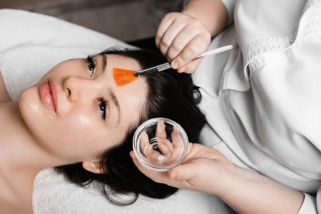 Mooie vrouw leunend op een spa-bed met geopende ogen terwijl ze een hyaluronzuur masker in een wellnesscentrum doet.
