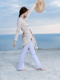 Mooie vrouw lichte kleren dragen op het zand in de buurt van de oceaan