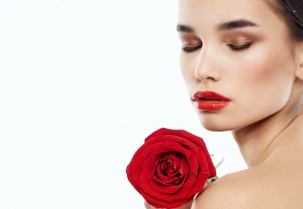 Mooie vrouw lichte make-up steeg in de hand schone huid poseren