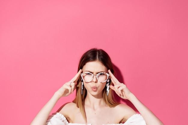 Mooie vrouw lichte make-up witte jurk roze achtergrond