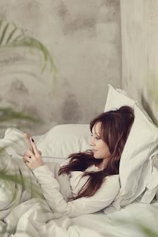Mooie vrouw liggend in het bed met smartphone