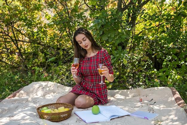 Mooie vrouw liggend op deken in de natuur genieten van vakantie met wijn op warme zomerdag