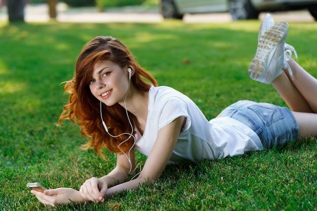 Mooie vrouw ligt op het gazon buiten in het park rest telefoon in handen