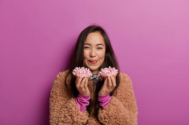 Mooie vrouw likt lippen met tong, houdt twee donuts vast, heeft een goede eetlust, geniet van suikerhoudende producten, anticipeert op een aangename smaak, heeft een vrolijke uitdrukking