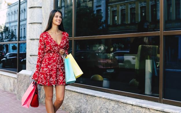 Mooie vrouw loopt langs de straat in een rode bloemenjurk, draagt verschillende boodschappentassen, glimlacht en kijkt ernaar uit