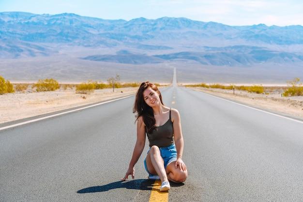 Mooie vrouw loopt langs een pittoreske lege weg in death valley met uitzicht op de bergen usa