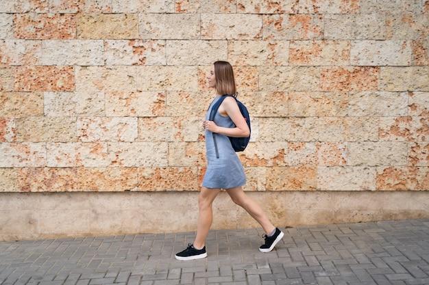 Mooie vrouw lopen met een rugzak in blauwe jurk wandelen in de stad op muur versierd met steen met mariene textuur