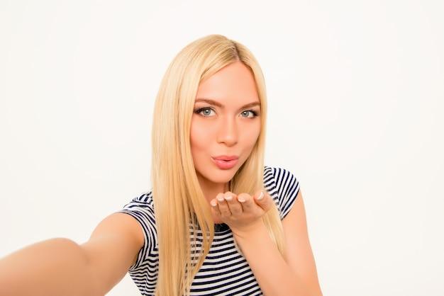 Mooie vrouw luchtkus verzenden tijdens het maken van selfie