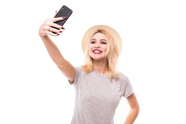 Mooie vrouw maakt een eend gezicht en neemt een selfie met haar smartphone